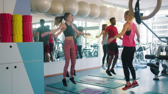 Men and Women Warming Up with Jumping Jacks at Gym