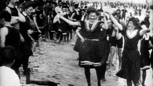men and women wearing 1900s bathing costumes skipping along water's edge laughing and holding hands in coney island new york - swimwear stock videos & royalty-free footage
