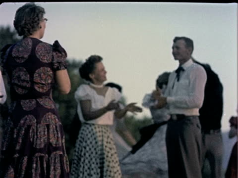 vídeos de stock e filmes b-roll de men and women wearing classic western clothing while square dancing outside / legs and feet of dancers. square dance hoedown on january 01, 1955 - dança quadrada