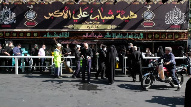 men and women wearing protective face masks stand on the lines for receiving donated meals while attending a religious ceremony to commemorate tasoua... - ashura muharram stock videos & royalty-free footage