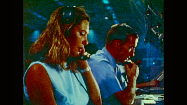 men and women wearing radio headsets monitor green lines on a video screen - ドキュメンタリー映画点の映像素材/bロール