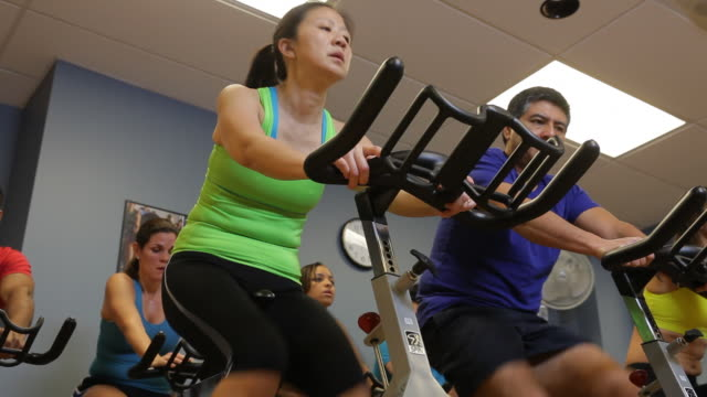 men and women work out on exercise bikes in a fitness center. - fitnesskurs stock-videos und b-roll-filmmaterial