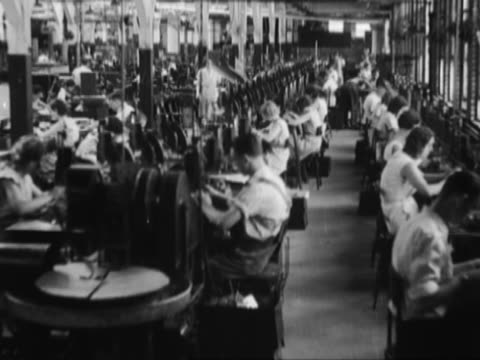 vidéos et rushes de men and women working in a factory - historique