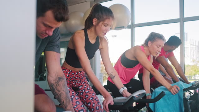 men and women working out on exercise bikes at gym - side by side stock videos & royalty-free footage
