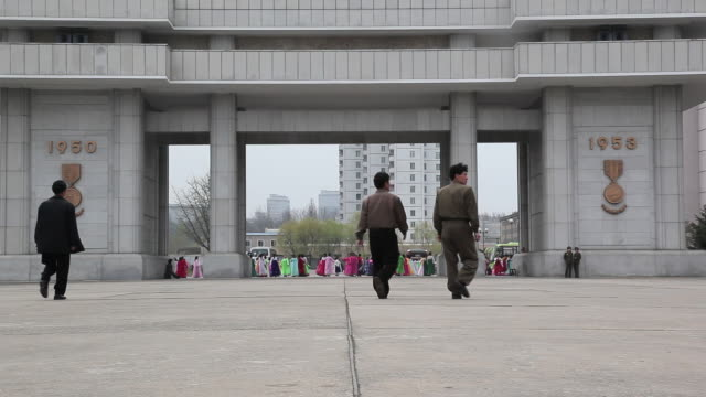Men approach the entrance to the Heroes Monument in Pyongyang.