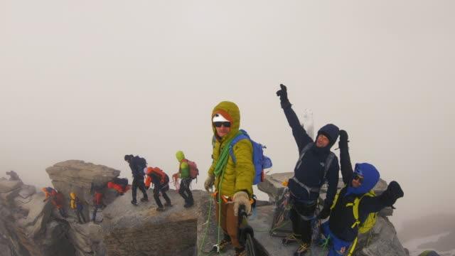 men are climbing to the top of the mountain - superare le avversità video stock e b–roll