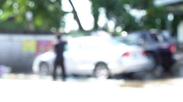 unfocused, men are washing the car. - pressure point stock videos & royalty-free footage