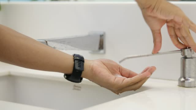Männer werden ihre Hände mit Flüssigseife waschen.