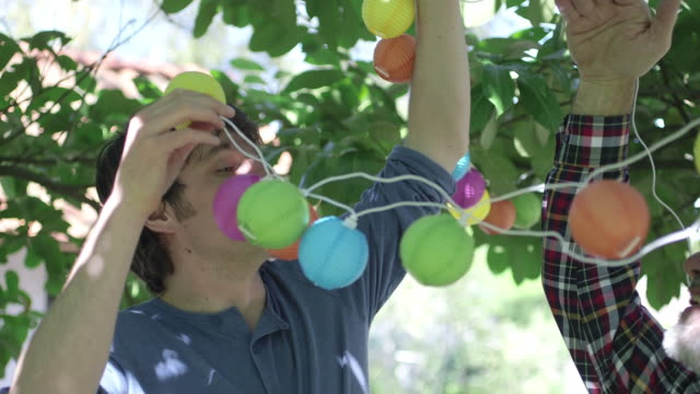 vídeos de stock e filmes b-roll de men arranging lights on tree - homens de idade mediana