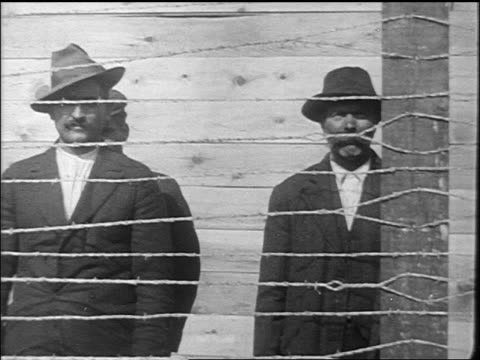 pan men arrested during palmer raids standing behind barbed wire fences / newsreel - anno 1920 video stock e b–roll