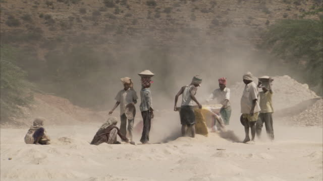 Men at an archaeological site sift the sand with a sheet.