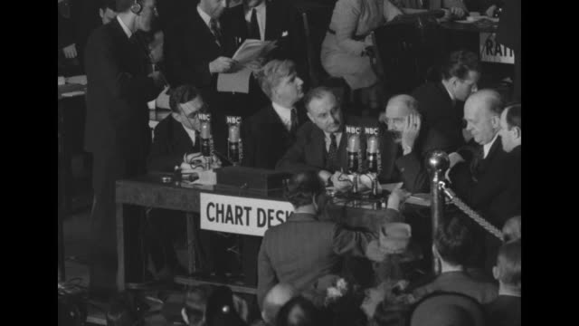 """men at """"chart desk"""" listening to commentator hans van kaltenborn who sits at desk with them, audience applauds during presidential election night... - nbc点の映像素材/bロール"""