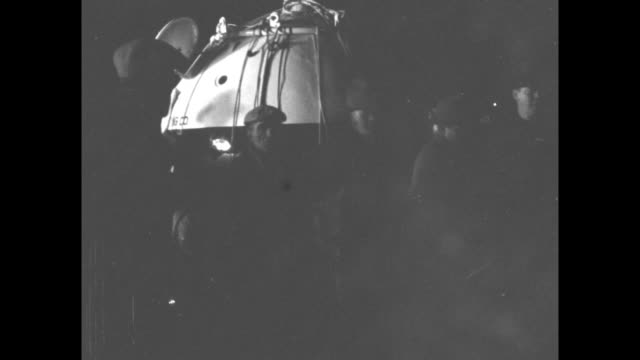 men at night inflating balloon / crowd standing in field watching / balloon inflating / two shots of men rolling gondola into position / balloon... - portello video stock e b–roll
