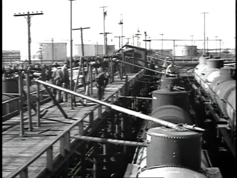 1929 montage men at refinery operating valves / united states - ölindustrie stock-videos und b-roll-filmmaterial