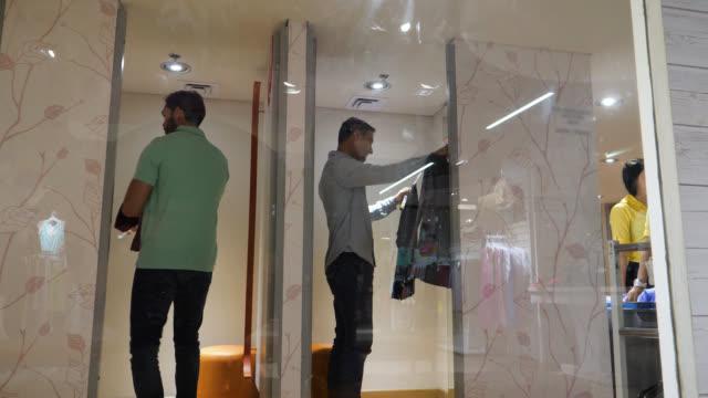 stockvideo's en b-roll-footage met mannen in de paskamer proberen kleren terwijl het kijken naar de spiegel - paskamer