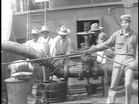 1923 ws men attaching large oil hose to valve on tanker / united states  - oil industry stock videos & royalty-free footage