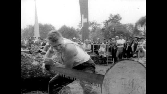 / men attempting to chop down trees with axes as crowd look on / contestants working in pairs to saw through giant tree limbs / two german... - spielkandidat stock-videos und b-roll-filmmaterial