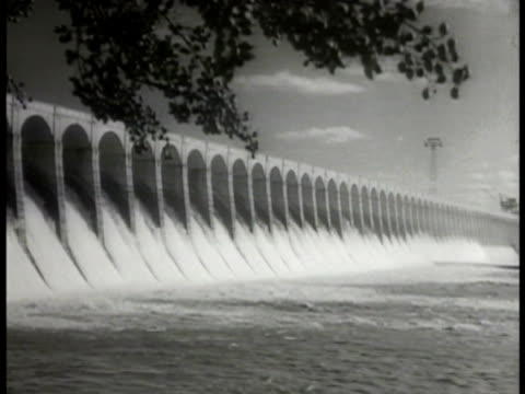 vidéos et rushes de men attending turbine generator in dam wilson dam w/ water flowing out electric power line tower men stringing electric power lines from bolt to tower - 1936