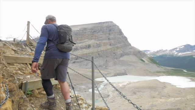 stockvideo's en b-roll-footage met men backpacking and hiking on a trail with trekking poles. - slow motion - men