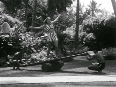 B/W 1939 2 men balancing woman in swimsuit practicing surfing on board on log / Hawaii / series