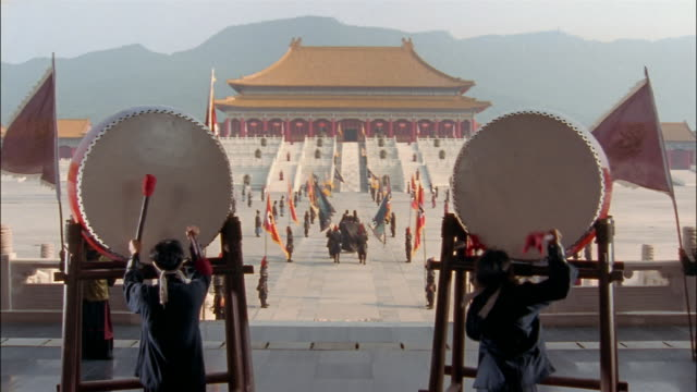 Men beat on drums as a procession walks toward the Hall of Supreme Harmony.
