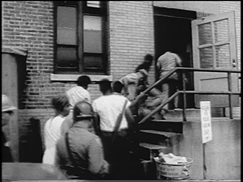 b/w 1967 men being arrested entering building newark race riots nj / newsreel - festnahme stock-videos und b-roll-filmmaterial