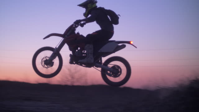 men being filmed with a drone while riding motocross motorcycles on a dirt off road at sunset. - slow motion - hungary stock videos & royalty-free footage