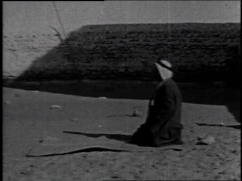 1936 WS Men bow down to pray, alone in the desert or in unison at the mosque