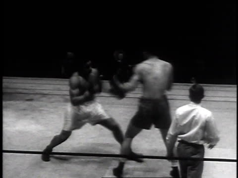 stockvideo's en b-roll-footage met men boxing / boxer is knocked out / referee helps boxer to his feet and across ring - 1935