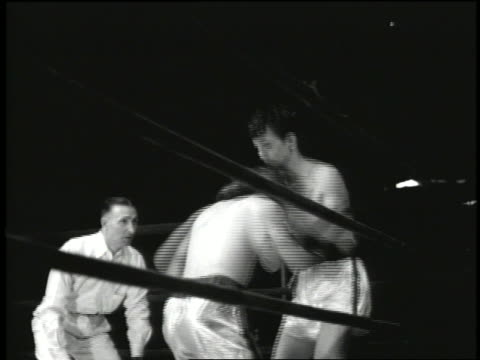 B/W 2 men boxing in ring / 1 goes down for count