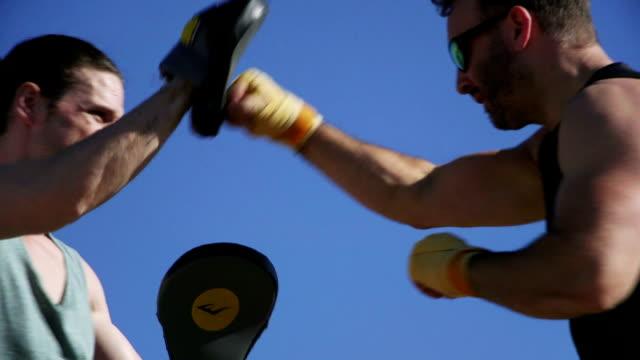 vídeos y material grabado en eventos de stock de hombres boxeo entrenamiento en la playa - puño gesticular