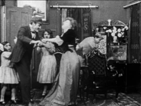 b/w 1909 men breaking into room where woman + girls are hiding / man + police come to rescue / film - gewalt stock-videos und b-roll-filmmaterial