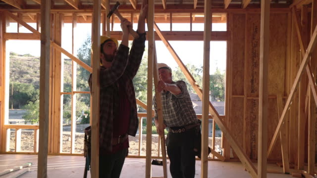 ws ts men building a house - costruire video stock e b–roll