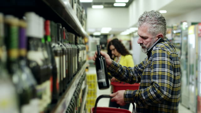 men buying bottle of wine and talking on smartphone - shelf stock videos and b-roll footage