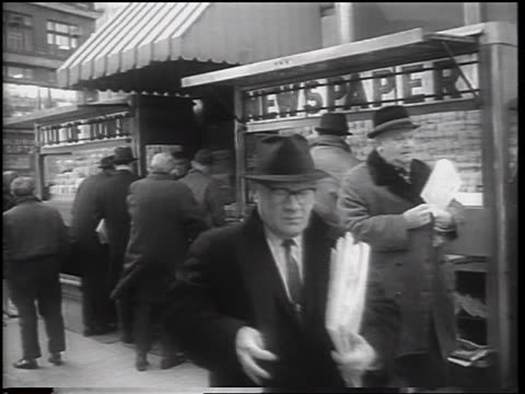 B/W 1962 men buying newspapers at newsstand on NYC sidewalk / newsreel