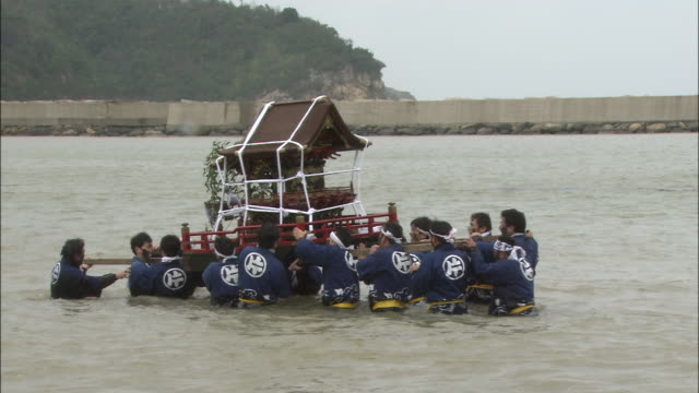 men carry a mikoshi in the sea. - shimane prefecture stock videos & royalty-free footage