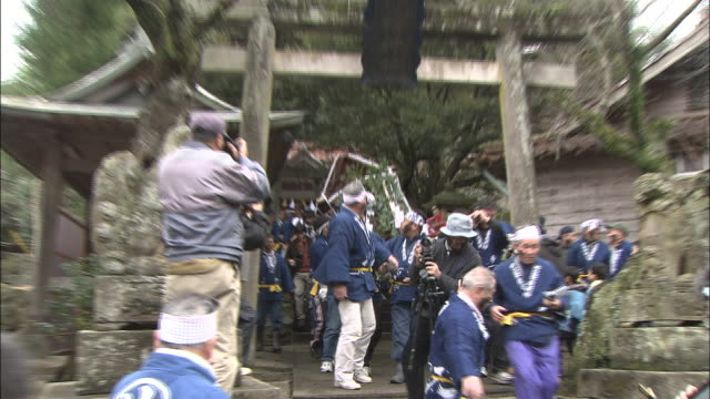 men carry a mikoshi through a gate during a shinto face painting rite. - shimane prefecture stock videos & royalty-free footage