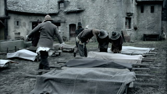 vídeos de stock, filmes e b-roll de men carry away stretchers with dead bodies on them. - reconstituição histórica
