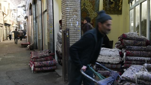 Men carry folded carpets on their shoulders and on trollies as they walk through the rug bazaar in Tehran Iran on Monday Jan 15 2018