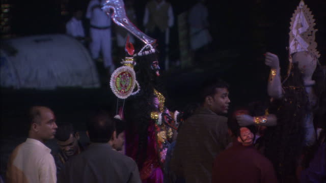 men carry large effigy of kali goddess across banks of ganges available in hd. - effigy stock videos & royalty-free footage