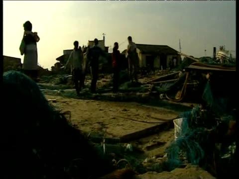 stockvideo's en b-roll-footage met men carry tsunami victim's corpse through debris in fishing net sling naggaputanam 2004 - hijsen
