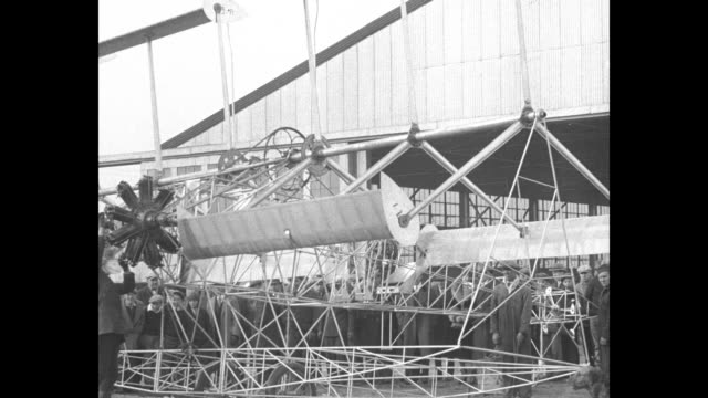 Men carrying airplane from hangar / man rotates paddle wings / CU inventor S P Nemeth posing for photo opportunity / two men securing rope attached...