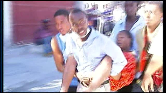 vidéos et rushes de men carrying along woman injured in earthquake - blessure physique