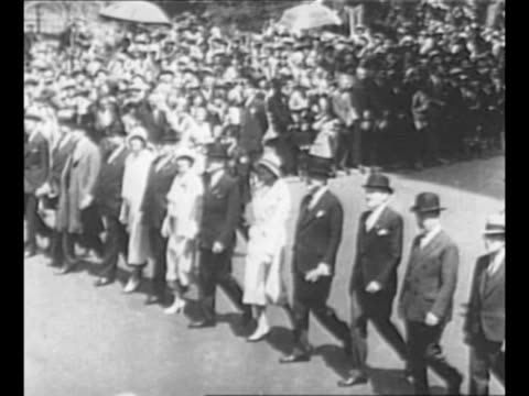 Men carrying banners march on New York City street during the Beer for Taxation parade / men in darkcolored business suits and women in lightcolored...