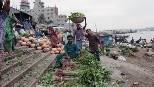 vídeos de stock, filmes e b-roll de men carrying baskets full of vegetables on their heads at the vegetable market on buriganga river bank, not far from the sadarghat boat terminal, dhaka, bangladesh, indian sub-continent, asia - bangladesh