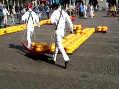 vidéos et rushes de men carrying large cheese rounds in historical cheese market, alkmaar, holland - culture néerlandaise