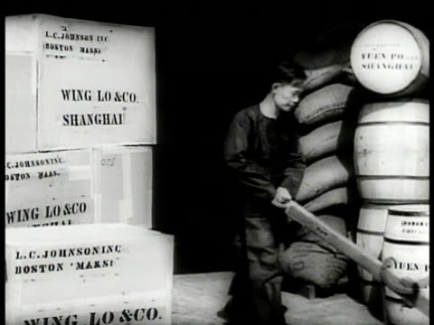 stockvideo's en b-roll-footage met men carrying logs to build wall ws worker w/ crates sacks barrels on dock ms man rolling barrel ms girl getting off sampan ws men carrying cargo to... - 1937