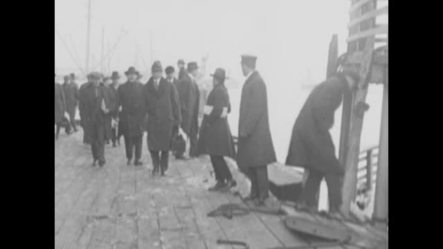 men carrying parcels, satchels, and luggage board a boat; the craft on its way to ellis island; a line of police all waving goodbye / note: exact... - exclusion stock videos & royalty-free footage