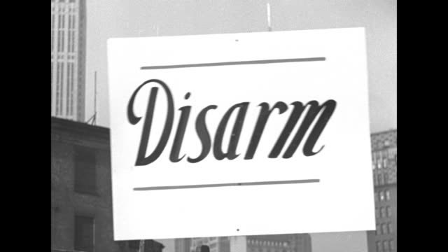vidéos et rushes de disarm down with armaments we want bread / street sign e 14 union sq w / vs newsboy with cigarette handing out copies of daily worker closer view of... - communisme