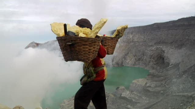 MS Men carrying sulfur from the mining at the ijen volcano towards toxic cloud / Ijen, Java, Indonesia